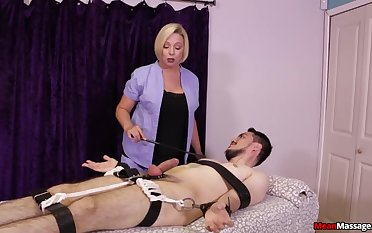 Strict blonde masseuse gives a Femdom handjob to a bound customer